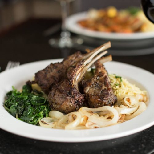 "Alt=""Lamb chops entree with basmati rice, grilled onions, and sauteed spinach."""