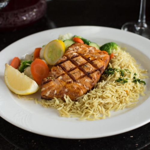 "Alt=""Grilled salmon dinner with basmati rice and steamed vegetables."""